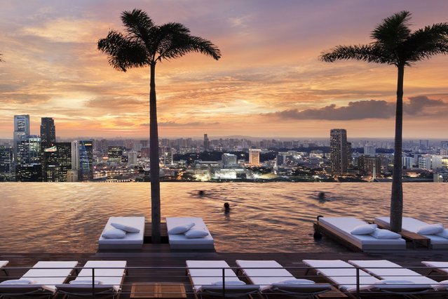 World's Greatest Swimming Pools: Marina Bay Sands, Singapore. This curved infinity pool located atop the Sands SkyPark is flanked by palm trees, plants and red lounge chairs on one side and Singapore's mesmerizingly dense cityscape on the other. Spanning the length of the hotel's three towers, it's the world's largest outdoor pool for its height – which is 656 feet, or 57 floors, in the air. (From $351). (Photo by Scott Frances/Marina Bay Sands)