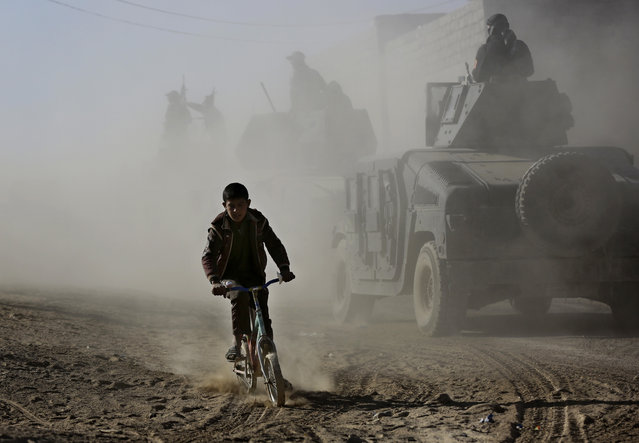 "An Iraqi boy rides his bicycle as he follows the special forces Humvees on their way to the front line to battle against Islamic State militants, in the Al-Samah neighborhood in Mosul, Iraq, Wednesday, November 23, 2016. An airstrike by the U.S.-led coalition on Wednesday ""disabled"" the fourth bridge on the Tigris River in Mosul, leaving the northern Iraqi city with a single functioning bridge, according to the Iraqi military and the Islamic State's media arm. (Photo by Hussein Malla/AP Photo)"