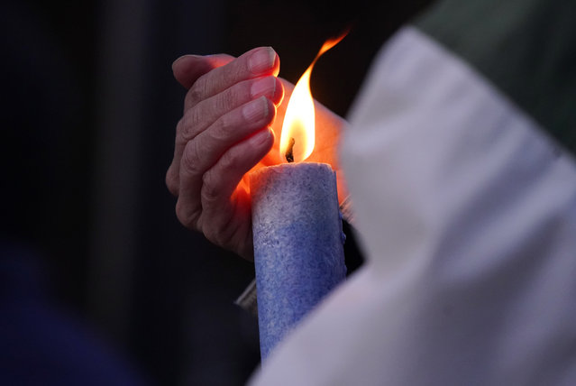 A mourner cups the flame from the wind while holding a candle at a vigil for the victims of a mass shooting in a grocery store earlier in the week, Wednesday, March 24, 2021, outside the courthouse in Boulder, Colo. (Photo by David Zalubowski/AP Photo)