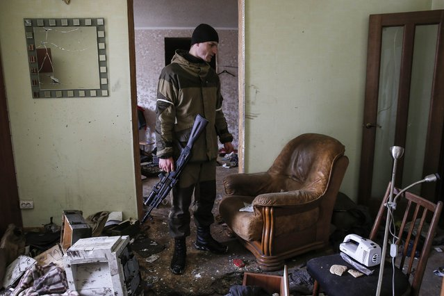 A pro-Russian separatist inspects a house, where Ukrainian troops held one of their positions, in the town of Horlivka, eastern Ukraine February 10, 2015. (Photo by Maxim Shemetov/Reuters)