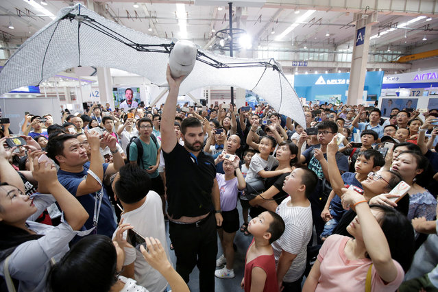 A robotic flying fox created by the German automation company Festo is carried through the crowd at the World Robot Conference (WRC) in Beijing, China on August 15, 2018. (Photo by Jason Lee/Reuters)