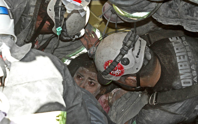 Firefighters rescues woman at home that collapsed after explosion  in Vila Brasilândia in the northern zone of São Paulo, on August 19, 2013. (Foto by Marcelo Alves/Techimage/Folhapress)