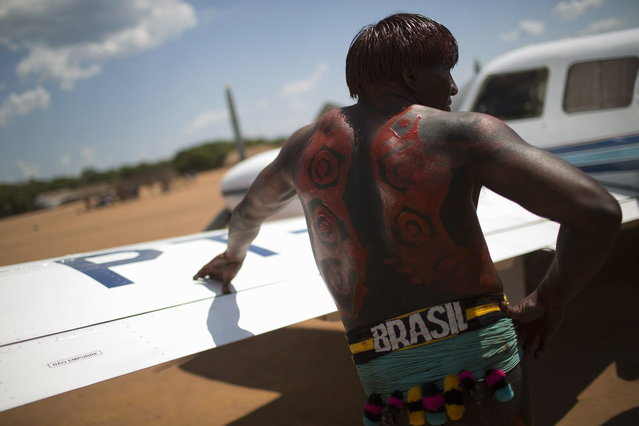 """A Waura Indian leans on the wing of a small plane during this year's """"quarup"""", a ritual held over several days to honour in death a person of great importance to them, in Xingu National Park, Mato Grosso State, August 25, 2013. This year the Waura tribe honoured their late cacique (chief) Atamai, who died in 2012, for his work creating the Xingu Park and his important contribution in facilitating communication between white Brazilians and Indians. (Photo by Ueslei Marcelino/Reuters)"""