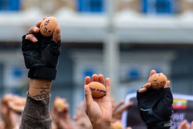 This photo taken and received courtesy of an anonymous source on April 4, 2021 shows protesters holding eggs with messages to coincide with Easter Sunday during a demonstration against the military coup in Taunggyi in Myanmar's Shan state. (Photo by Handout/Anonymous via AFP Photo)