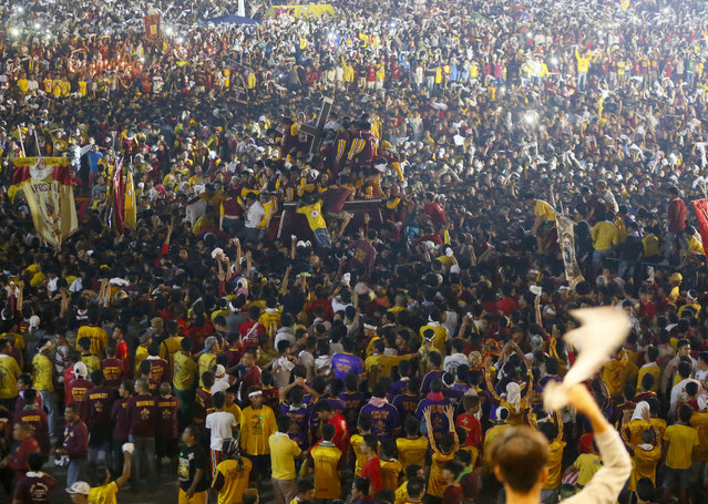 Tens of thousands of Catholic devotees jostle to get closer to the image of the Black Nazarene as they take part in a raucous procession to celebrate its feast day in Manila, Philippines, Saturday, January 9, 2016. (Photo by Bullit Marquez/AP Photo)