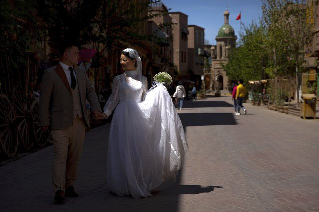 A woman in a bridal outfit walks as she poses for wedding photos in the old city in Kashgar in western China's Xinjiang Uyghur Autonomous Region, as seen during a government organized trip for foreign journalists, Monday, April 19, 2021. (Photo by Mark Schiefelbein/AP Photo)