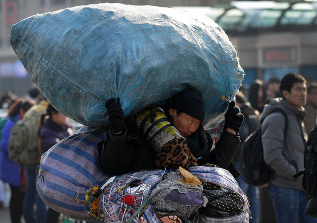 A migrant carries his belongings as he arrives at the Beijing railway station to catch a train in Beijing, Friday, February 13, 2015. (Photo by Andy Wong/AP Photo)