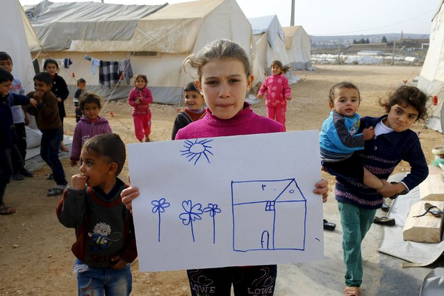 Syrian refugee girl Rahaf Hasan, 10, poses as she holds a drawing of her home in Syria in Midyat refugee camp in Mardin province, Turkey, December 14, 2015. (Photo by Umit Bektas/Reuters)