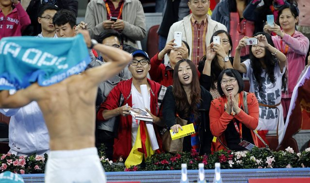 Fans watch Spain's Rafael Nadal change his shirt after he defeated Philipp Kohlschreiber of Germany in their match at the China Open tennis tournament in Beijing October 2, 2013. (Photo by Kim Kyung-Hoon/Reuters)