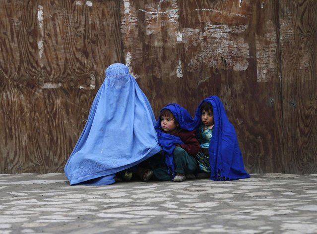 An Afghan woman wearing a burqa waits for transportation with her children on a cold day in Kabul January 22, 2015. (Photo by Mohammad Ismail/Reuters)