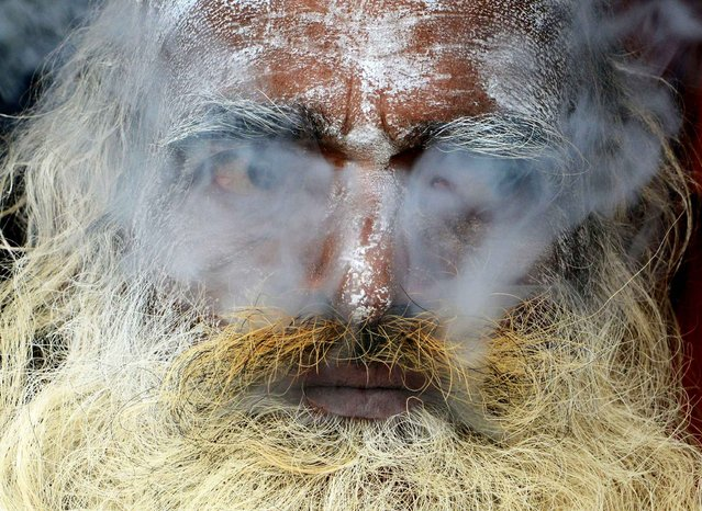 An Indian sadhu (Hindu holy man) smokes cannabis at his temporary camp on Gangasagar Island, around 150 km south of Kolkata, on January 13, 2016. More than 500,000 Hindu pilgrims and sadhus are expected to gather at the confluence of the River Ganges and the Bay of Bengal during the Gangasagar Mela to take a 'holy dip' in the ocean on the occasion of Makar Sankranti, a holy day of the Hindu calendar considered to be of great religious significance in Hindu mythology. (Photo by Dibyangshu Sarkar/AFP Photo)