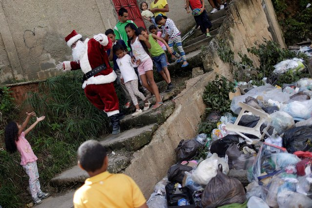 Santa Claus greets a child during a visit to residents of the slum of Petare in Caracas, Venezuela, December 11, 2016. (Photo by Ueslei Marcelino/Reuters)