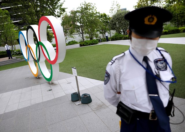 Security personnel stand guard near the Olympic rings monument during a rally by anti-Olympics protesters outside the Japanese Olympic Committee headquarters, amid the coronavirus disease (COVID-19) outbreak, in Tokyo, Japan May 18, 2021. (Photo by Issei Kato/Reuters)