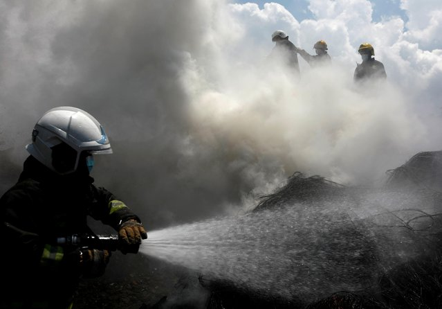 Smoke rises as firefighters try to douse a fire on a pile of wires at the premises of Environment Health and Health Care Waste Management Section in Kathmandu, Nepal on June 3, 2021. (Photo by Navesh Chitrakar/Reuters)
