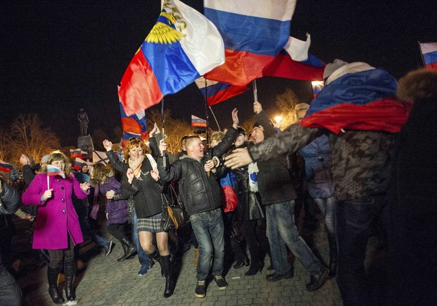 In this Sunday, March 16, 2014 file photo pro-Russian people celebrate in the central square in Sevastopol, Crimea, as residents in Crimea voted overwhelmingly to secede from Ukraine and join Russia. (Photo by Andrew Lubimov/AP Photo)