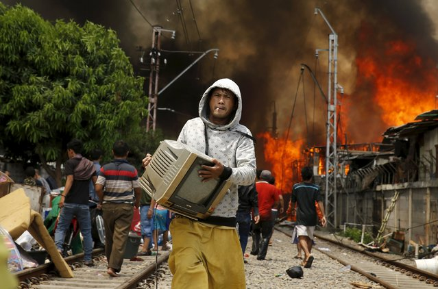 A man carries a television away from a fire in a slum area next to railway tracks in Kampung Bandan, North Jakarta, Indonesia January 26, 2016. (Photo by Reuters/Beawiharta)
