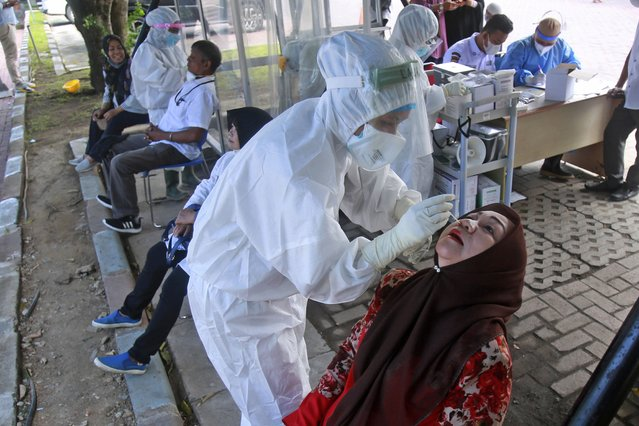 A medical workers collect nasal swab samples from a woman to be tested for coronavirus during a COVID-19 screening at University of North Sumatra in Medan, Indonesia, Monday, June 21, 2021. Indonesia has reported more coronavirus cases than any other country in Southeast Asia. (Photo by Binsar Bakkara/AP Photo)