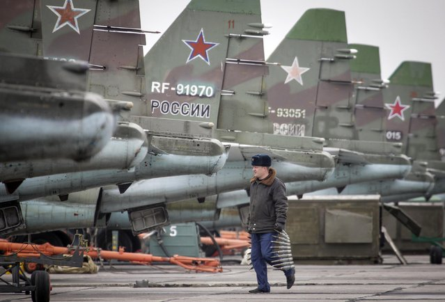 A serviceman carries ammunition next to Sukhoi Su-25 jet fighters during a drill at the Russian southern Stavropol region, March 12, 2015. (Photo by Eduard Korniyenko/Reuters)