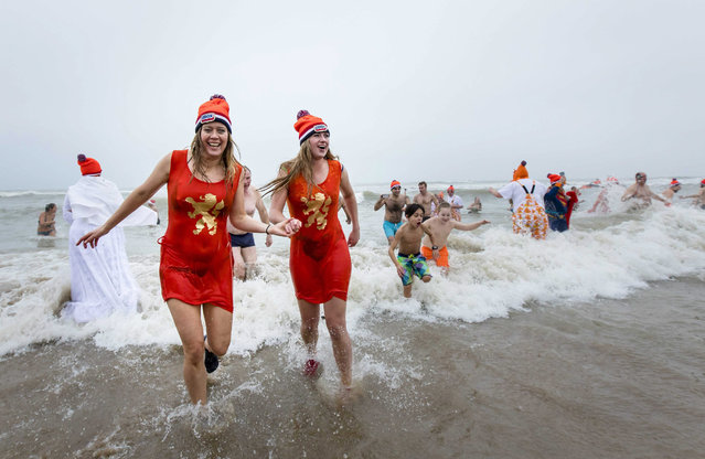 Costumed people get out of the North Sea during the Nieuwjaarsduik (New Year's Dive) on New Year's Day in Scheveningen, the Netherlands, 01 January 2017. (Photo by Bart Maat/EPA)