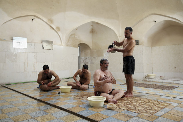 In this Friday, November 21, 2014 photo, Heidar Javadi, 39, a bathhouse worker pours warm water on a man at the Setareh public bathhouse, in Yazd, Iran. (Photo by Ebrahim Noroozi/AP Photo)