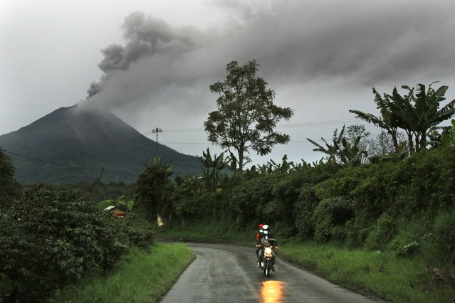 Motorists ride pass by as Mount Sinabung spews volcanic ash into the air in Tiga Pancur, North Sumatra, Indonesia, Tuesday, November 26, 2013. Authorities raised the alert status of the volcano to the highest level on Sunday after it had a series of eruptions. (Photo by Binsar Bakkara/AP Photo)