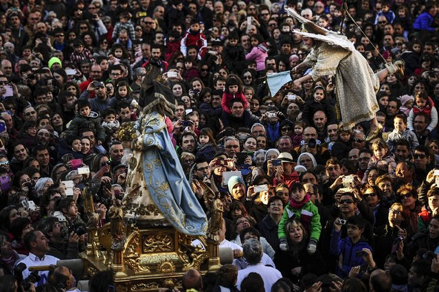 """8 years old Alba Oroz, secured by a harness, is transported in the air, above the crowd as she unveils the face of a statue of the Virgin Mary, during the Easter Sunday ceremony """"Descent of the Angel"""", during Holy Week in the small town of Tudela, northern Spain, Sunday, April 5, 2015. (Photo by Alvaro Barrientos/AP Photo)"""