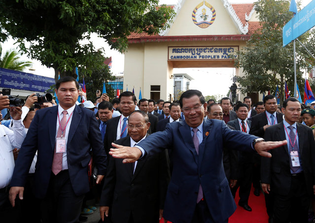 President of the Cambodian People's Party (CPP), Prime Minister Hun Sen (center R) and CPP Honorary President and President of the National Assembly Heng Samrin (center L) arrive before a ceremony at the party headquarters to mark the 38th anniversary of the toppling of Pol Pot's Khmer Rouge regime in Phnom Penh, January 7, 2017. (Photo by Samrang Pring/Reuters)