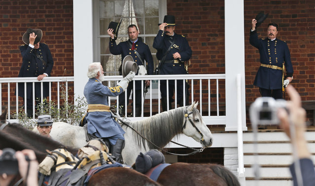 Thomas Lee Jessee, portraying Confederate General Robert E. Lee, front, tips his hat to Union officers on the porch of the McLean house as part of the commemoration of the 150th anniversary of the surrender of the Army of Northern Virginia at Appomattox Court House in Appomattox, Va., Thursday, April 9, 2015. Lee left the house after meeting with Union General Ulysses S. Grant  after signing the surrender documents. (Photo by Steve Helber/AP Photo)