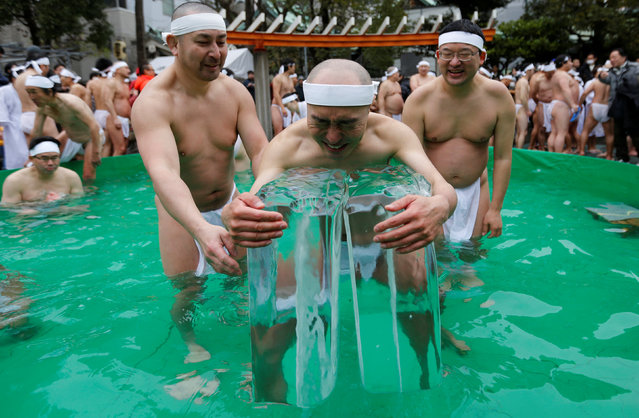 Men wearing loin cloths hold on to ice as they bathe in ice-cold water outside the Teppozu Inari shrine in Tokyo, Japan, January 8, 2017. (Photo by Toru Hanai/Reuters)