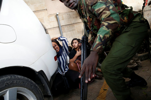 People are evacuated by a member of security forces at the scene where explosions and gunshots were heard at the Dusit hotel compound, in Nairobi, Kenya on January 15, 2019. (Photo by Baz Ratner/Reuters)