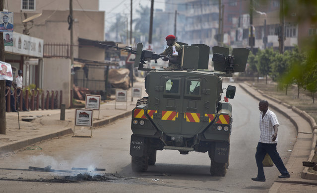A Ugandan soldier points a heavy-calibre machine gun in the direction of supporters of opposition leader Kizza Besigye, as he drives in an armored personnel carrier in Kampala, Uganda, Friday, February 19, 2016. (Photo by Ben Curtis/AP Photo)