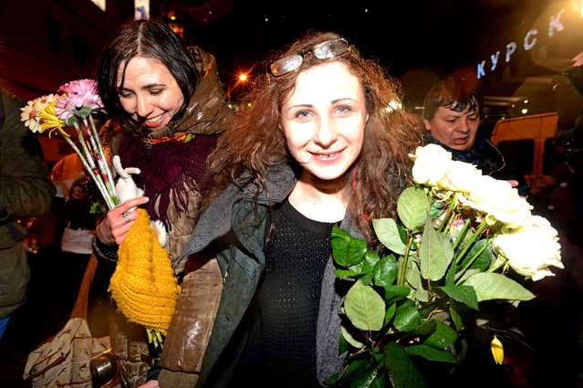 Maria Alyokhina (C), one of the jailed members of anti-Kremlin punk band p*ssy Riot, is surrounded by journalists and her supporters as she arrives in Moscow on December 23, 2013. Alyokhina, who was freed from prison under a Kremlin-backed amnesty slammed the measure as a mere publicity stunt and said that she would have preferred to remain in prison. (Photo by Kirill Kudryavtsev/AFP Photo)