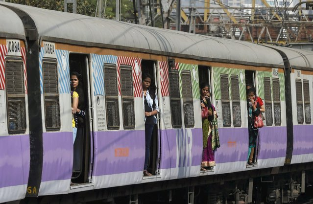 Commuters stand on the doors of a suburban train as it approaches the Churchgate railway station in Mumbai, India, February 25, 2016. (Photo by Shailesh Andrade/Reuters)