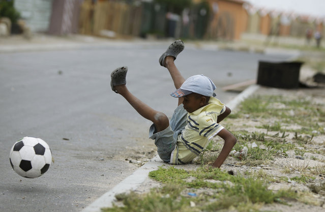 A boy tumbles as he plays soccer on the streets of the Khayelitsha township in Cape Town, December 3, 2009. (Photo by Kai Pfaffenbach/Reuters)