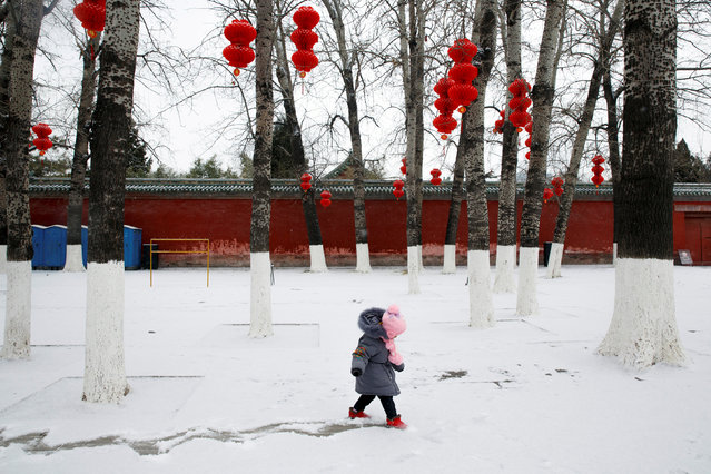 A girl draws a track into the snow in Ditan Park in Beijing, China, February 12, 2019. (Photo by Thomas Peter/Reuters)