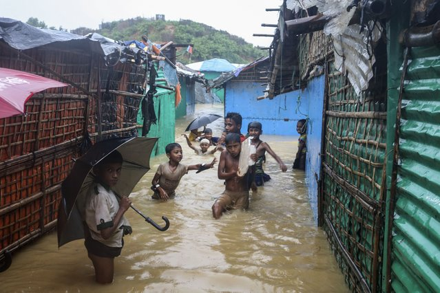 Rohingya refugee children play in flood waters at the Rohingya refugee camp in Kutupalong, Bangladesh, Wednesday, July 28, 2021. Days of heavy rains have brought thousands of shelters in various Rohingya refugee camps in Southern Bangladesh under water, rendering thousands of refugees homeless. (Photo by Shafiqur Rahman/AP Photo)