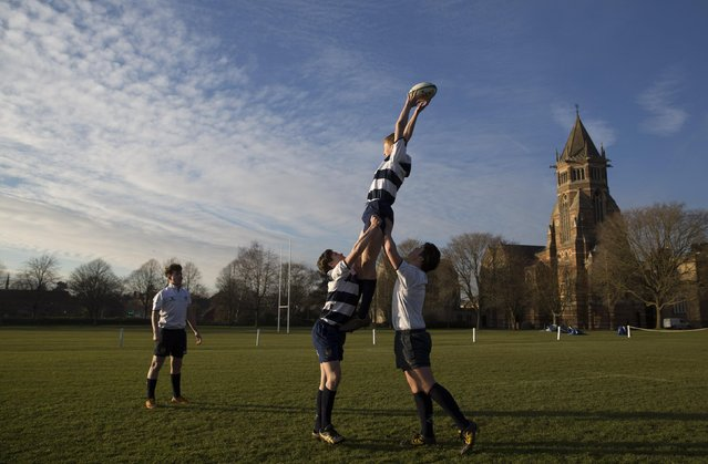 A pupil catches a ball as he takes part in rugby practice on the playing fields of Rugby School in central England, January 20, 2015. (Photo by Neil Hall/Reuters)
