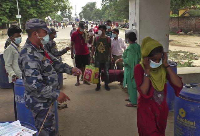 Nepalese policemen check before allowing people to cross the border to enter India, at Nepalgunj border town, Nepal, Wednesday, July 7, 2021. (Photo by Krishna Adhikari/AP Photo)