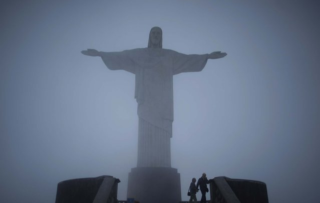 Tourists stand below the Christ the Redeemer statue on September 29, 2010. (Photo by Natacha Pisarenko/Associated Press)