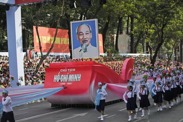 """School children walk alongside a float carrying a portrait of  Vietnamese national hero Ho Chi Minh during a parade celebrating the 40th anniversary of the end of the Vietnam War which is also remembered as the """"Fall of Saigon"""", in Ho Chi Minh City, Vietnam, Thursday, April 30, 2015. (Photo by Dita Alangkara/AP Photo)"""