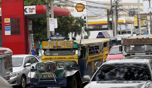Motorists drive past an electronic board at a gas station in Paranaque city, Metro Manila, the Philippines February 4, 2016. A litre of diesel is priced at 19.2 pesos ($0.40) a litre. A dramatic drop in oil prices, driven down by a glut in supply, is translating into a mixed bag for motorists. All countries have access to the same oil prices on international markets, but retail prices vary wildly, largely because of taxes and subsidies. (Photo by Erik De Castro/Reuters)