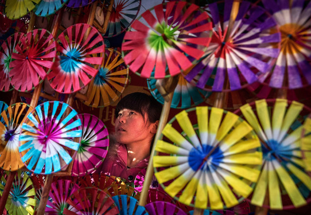 A Chinese woman sells traditional handheld windmills at a local temple fair on the fifth day of the Chinese Lunar New Year on February 1, 2017 in Beijing, China. China is marking the year of the Fire Rooster. (Photo by Kevin Frayer/Getty Images)