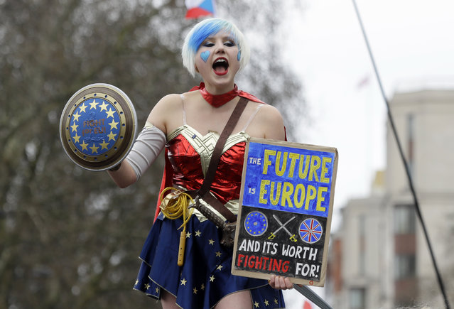 A demonstrator holds a holds a poster during a Peoples Vote anti-Brexit march in London, Saturday, March 23, 2019. (Photo by Kirsty Wigglesworth/AP Photo)