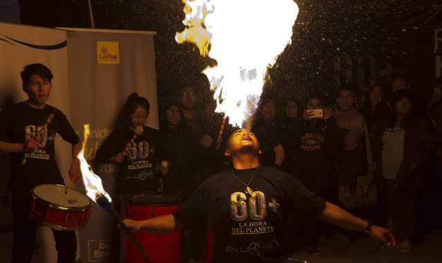 A fire eater performs during the Earth Hour celebrations in La Paz, Bolivia, Saturday, March 30, 2019. Earth Hour takes place worldwide and is a global call to turn off lights for 60 minutes in a bid to highlight the global climate change. The Earth Hour was started in Australia in 2007, which has become a global event. (Photo by Juan Karita/AP Photo)