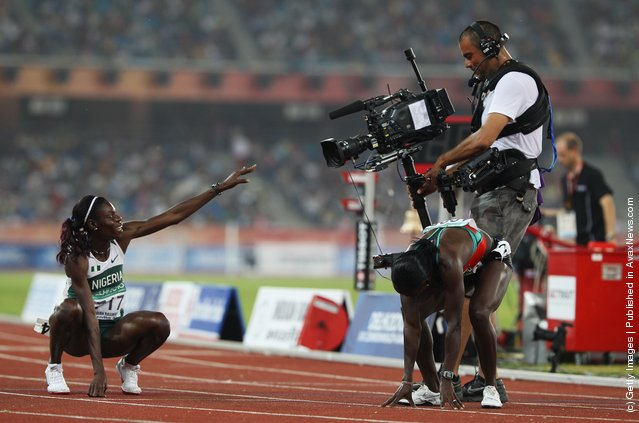 Gold medalist Muizat Odumosu of Nigeria points to a camera as she celebrates winning the women's 400 metres hurdles at Jawaharlal Nehru Stadium during day seven of the Delhi 2010 Commonwealth Games on October 10, 2010 in Delhi, India
