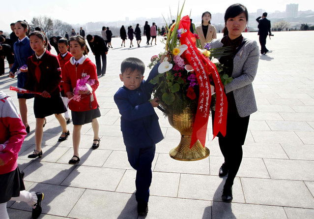 People carry flowers to pay tribute to the statues of former leaders Kim Il Sung and Kim Jong Il on Mansu Hill to mark the Day of the Sun in Pyongyang, Monday, April 15, 2019. (Photo by Jon Chol Jin/AP Photo)