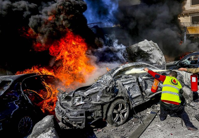 A Hezbollah civil defense worker extinguishes a burned car at the site of an explosion, near the Kuwaiti Embassy and Iran's cultural center, in the suburb of Beir Hassan, Beirut, Lebanon, Wednesday, February 19, 2014. A blast in a Shiite district in southern Beirut killed at least two people on Wednesday, security officials said – the latest apparent attack linked to the civil war in neighboring Syria. (Photo by Hussein Malla/AP Photo)