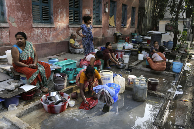 Residents of an area gather around a roadside water source to wash their clothes and fill drinking water for their houses in Kolkata, India, Tuesday, March 22, 2016. (Photo by Bikas Das/AP Photo)