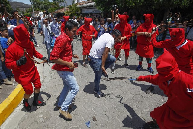"""A group of men performing in costume  as traditional characters called Talciguines, a representation of the devil, whip a man branded as a """"sinner"""" as part of the Holy Monday, a tradition in the town of Texistepeque, 83 kilometeres from San Salvador, El Salvador, 21 March 2016. The Holy Week tradition in the town features theatrical representations of the fight between good and evil. (Photo by Oscar Rivera/EPA)"""
