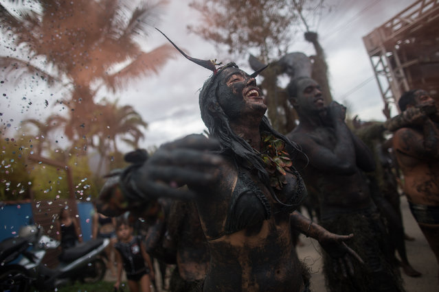 Revelers participate in the traditional 28th  Bloco da Lama (Mud block) carnival in  on March 1, 2014 Parati, Rio de Janeiro State, Brazil. The event, which was begun by two men in a playful manner in 1986, has now become a traditional carnival in which participants disguised as primitives with rags, lianas or skulls and bones, dive in the mud. (Photo by Victor Moriyama/Getty Images)